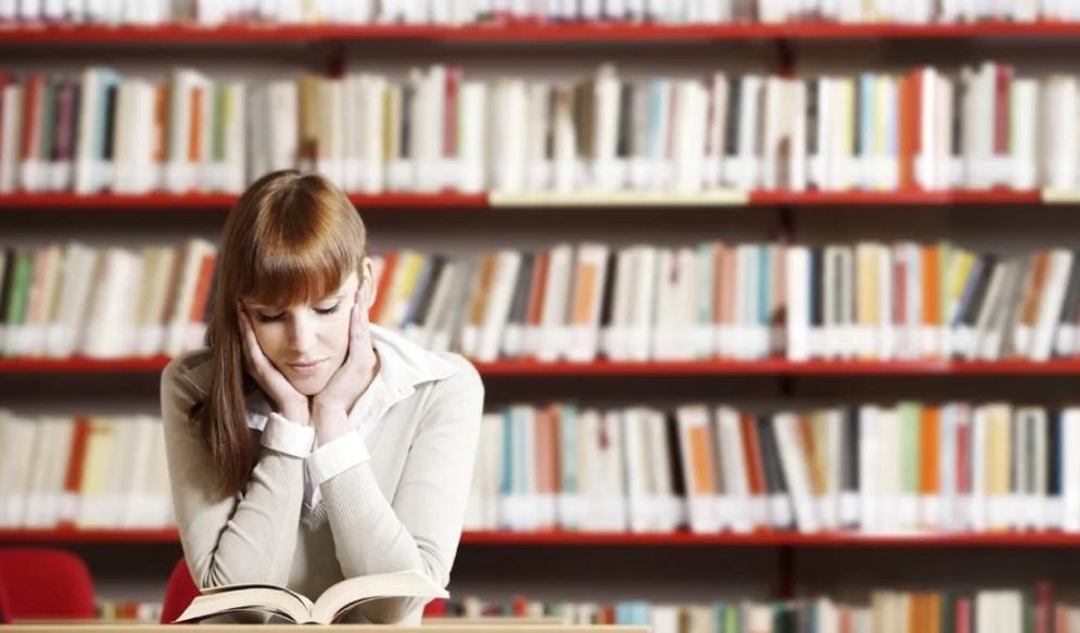 Femme qui lit dans une bibliothèque