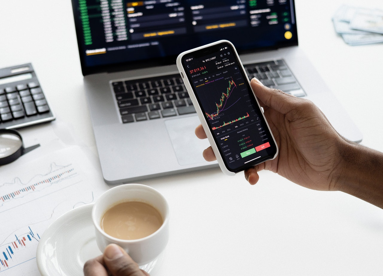personne tenant smartphone investissement trading